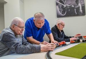 Three men put the CN model train on the track