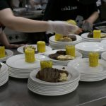 Kitchen staff prepares the dinner plates with corn on the cob, steak, and potatoes for the 2017 Canada Day Barbecue