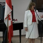 A lady dressed festively for Canada Day speaks into a microphone