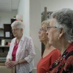 Three ladies sing O' Canada