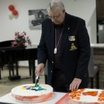 A veteran cuts the Canada Day cake at the Rotary Villas celebration 2017