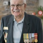 A veteran and resident of Rotary Villas poses with his medals