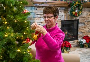 A lady places decorations on the branches of the Christmas tree