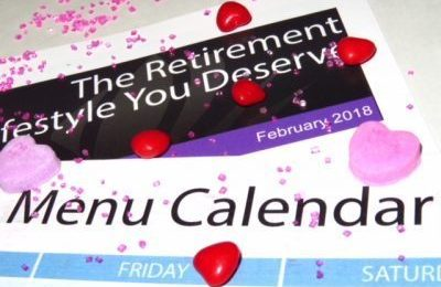 Valentine candy lays on top of a February activity calendar and menu calendar