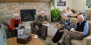 A group of four seniors sit and have coffee and chat in front of the fireplace