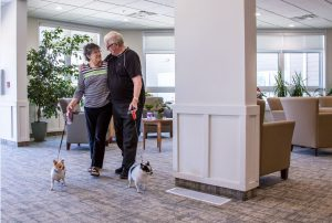 A man and women walk two small dog through the hallway of Rotary Villas. Rotary Villas has designated pet-friendly suites.