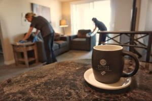A Rotary Villas coffee mug sits in focus while two ladies clean a suite