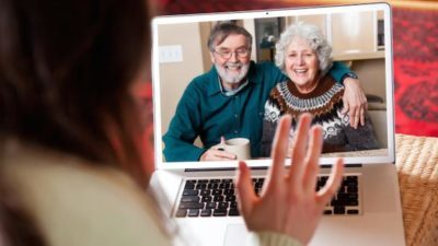 A lady waves at relatives on Skype