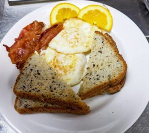 Bacon, eggs, and toast with a couple orange slices.