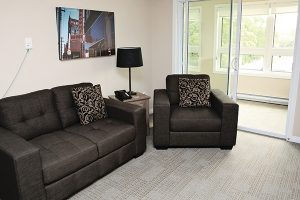 A typical living room setup consisting of a loveseat, end table, and chair in one of the Rotary Villas suites